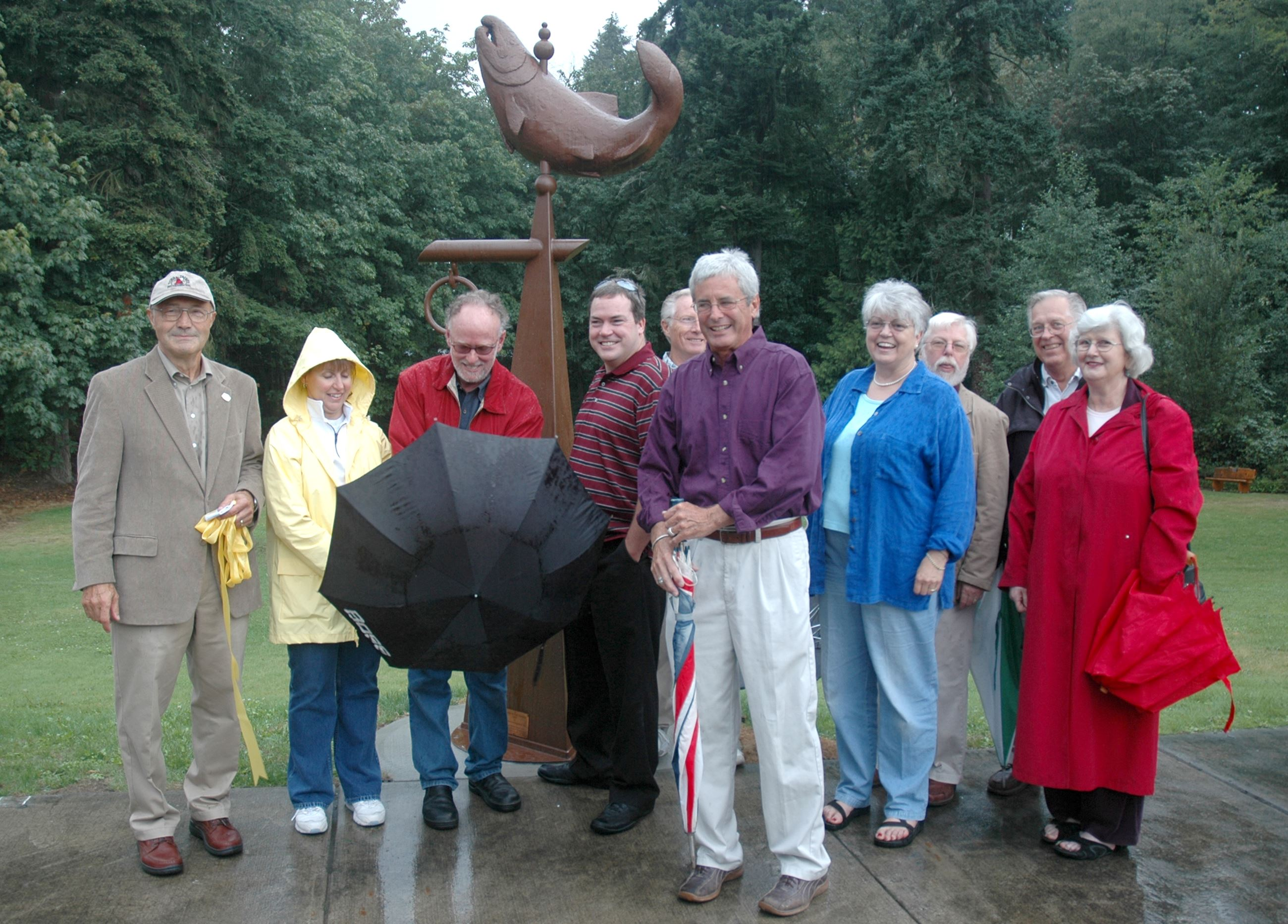 Mayor Chuck Hunter far left, Artist Tom Torrens with umbrella and Ben Isitt stand with other members